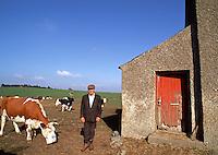 An Irish farmer stands outside of his home as cows graze around him. Davistown, Ireland.