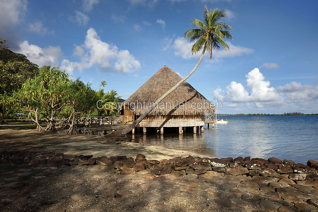 Fare Pote'e, a reconstruction of a round communal dwelling, built on stilts with a thatched roof, on the banks of Lake Fauna Nui or Maeva Lake, at the archaeological site at Maeva village, on Huahine-Nui on the island of Huahine, in the Leeward Islands, part of the Society Islands, in French Polynesia. The Fare Pote'e has been used as a house, meeting room, church, school and museum and has been rebuilt several times, most recently in 2000-01 by the Opu Nui Association. Maeva is thought to be an abandoned royal settlement, with many megalithic structures including marae, houses, agricultural structures, stone fish traps and fortification walls. Picture by Manuel Cohen