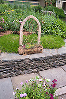 Rustic garden ornament containers, stone wall, flower beds, shed, walkway, trellis, flea market finds using old things in the garden as pots