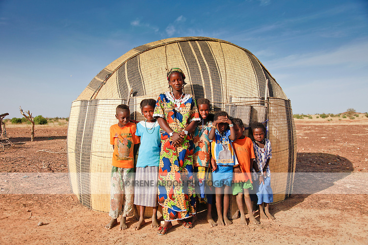 In the Fulani village of Jolooga in northern Burkina Faso, villagers stand outside a traditional house made from woven mats of straw.  Traditionally pastoralist, this house can be disassembled and reassembled at will, as the family and their livestock crisscross the Sahel in search of fresh water and green pastures.