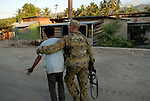 After losing his house and belongings to a random act of arson at Comoro, a young man is comforted by an Australian soldier outside the location of Prime Minister Mari Alkatiri's party meeting and press conference. Comoro, Dili, East Timor 04/06/06