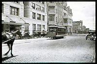 In this 1913 photo, a horse carriage drives on the cobblestone streets past the Littlefield Building as a cable car drives past the Dristill Hotel on Sixth Street in downtown Austin Texas.