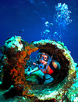 Diver Sally Herschorn peaks through the remains of a sunken ship in the Bahamas.  Model release on file..