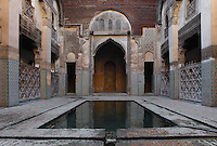 Low angle view of pool in main courtyard, Sahrij Medersa, (Medersa des Andalous), 1321, Fez, Morocco, pictured on February 23, 2009 in the morning. The Sahrij Medersa takes its name from the pool in its courtyard, (sahrij means basin). Green and white minarets crown the theological school founded by Merinid sultan Abou al-Hassan and attached to the Al-Andalous mosque.  It is decorated with ornate  dark cedar panels (mashrabiya), decorated tiles (zellij), marble pavings and intricate plasterwork. Fez, Morocco's second largest city, and one of the four imperial cities, was founded in 789 by Idris I on the banks of the River Fez. The oldest university in the world is here and the city is still the Moroccan cultural and spiritual centre. Fez has three sectors: the oldest part, the walled city of Fes-el-Bali, houses Morocco's largest medina and is a UNESCO World Heritage Site;  Fes-el-Jedid was founded in 1244 as a new capital by the Merenid dynasty, and contains the Mellah, or Jewish quarter; Ville Nouvelle was built by the French who took over most of Morocco in 1912 and transferred the capital to Rabat. Picture by Manuel Cohen.