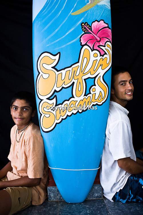 """(Left to right) Satyaraj and Daruka pose with the """"Surfin' Swamis"""" surfboard at the Kaliya Mardana Krishna Ashram in the coastal town of Mulki, just north of Mangalore, Karnataka, India.  ..Krishna devotees in the Gaudiya Vaishnava tradition of Hinduism, they are known collectively as the """"surfing swamis."""" The """"surfing ashram"""" is growing in popularity and surfing here is a form of meditation, a spiritual practice leading to heightened states of awareness."""