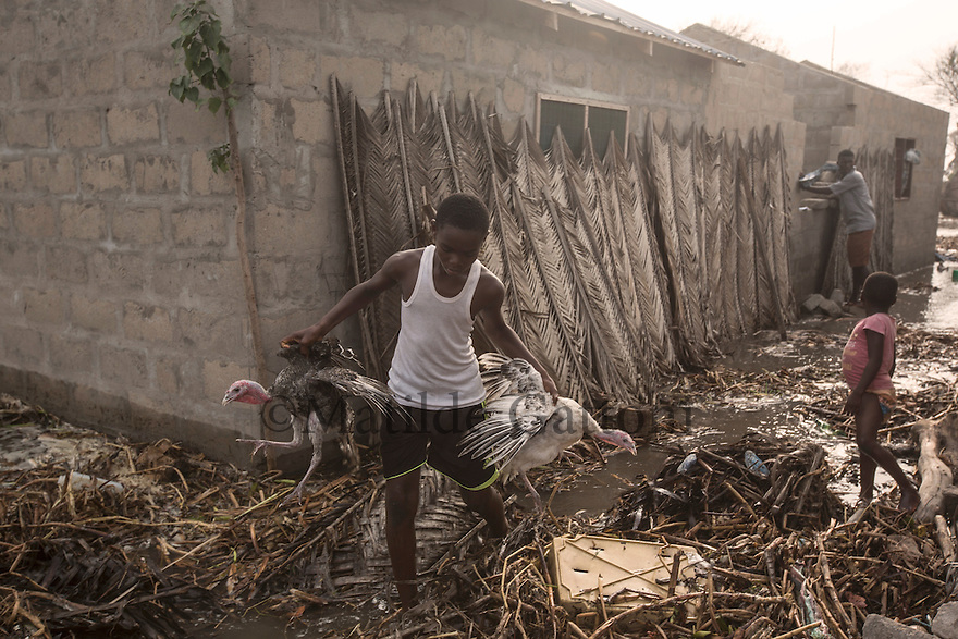 Ghana - Fuveme - A young boy carries his two turkeys to save them from the flood caused by the rising sea level.<br /> <br /> Nestled between the ocean and the Volta river estuary, the village of Fuvemeh has seen its territory reduced from several kilometers to few hundred meters. Nowadays, the villages sits on a narrow strip of land which separates the coastline from the adjacent lagoon. Haunted by coastal erosion, its 1,000 inhabitants have literally nowhere to move.