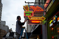 "A man secures a neon restaurant sign prior to Hurricane Sandy in Chelsea in New York on Sunday, October 28, 2012. In advance of the arrival of Hurricane Sandy New York will down the subways at 7 PM on Sunday and evacuate low lying ""Zone A"" areas including Battery Park City. In addition the schools will be closed on Monday. (© Frances M. Roberts)"