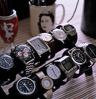 Detail of a collection of wrist watches displayed in rows on a table in the bathroom