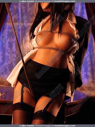 Beautiful half-naked young asian woman standing at a table tied with Japanese Shibari rope bondage