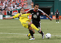 WASHINGTON, DC - AUGUST 4, 2012:  Dwayne DeRosario (7) of DC United is tackled by Carlos Mendes (4) of the Columbus Crew during an MLS match at RFK Stadium in Washington DC on August 4. United won 1-0.