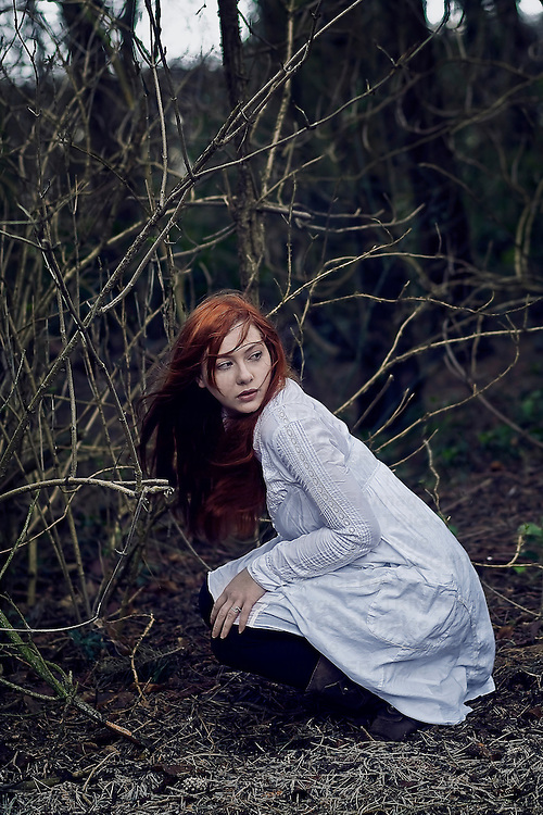 A girl wearing a white dress in the forest crouching.