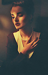 Young woman with 60's period look wearing pearl necklace with hand on heart looking down with sad expression