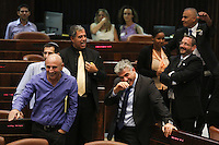 Israeli Finance Minister Yair Lapid (C) and Yesh Atid MK Ofer Shelah (L) gesture during a plenum session voting on the state budget, in the Knesset, Israel's Parliament, in Jerusalem, late night July 29, 2013. The Knesset approved the State Budget at second and third readings in the early hours of Tuesday morning in a 58-43 vote, following a 15-hour parliamentary session. Photo by Oren Nahshon