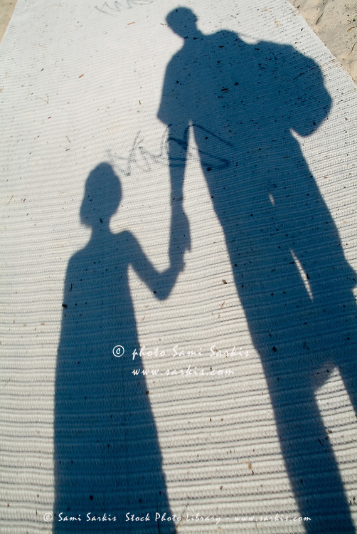 Shadow of a father and his daughter walking on a mat ...