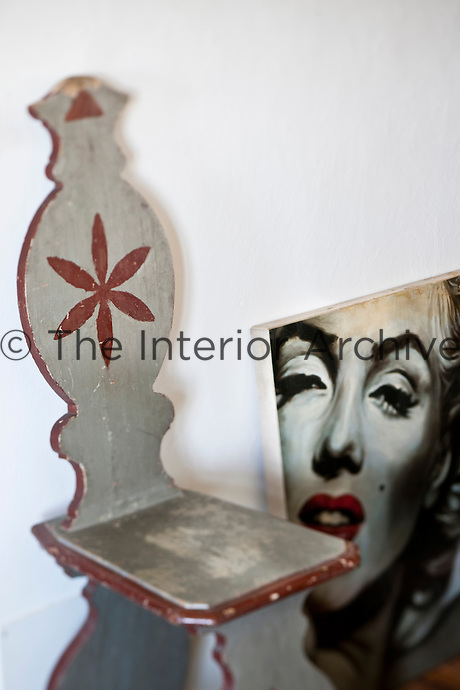 A wooden chair typical of the region with a photograph of Marylin Monore resting against the wall