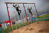 Competitors dressed as revolutionary militia climb a rope net in the obstacle course event of the Red Games. Held in Junan County, this sporting event is a nostalgic tribute to the communist era.