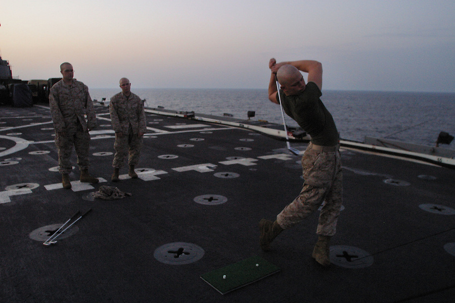 """A Marine works on his swing sending balls arcing off the rear of the USS Denver's flight deck. The balls and clubs are provided by the ship's """"Morale, Wellfare, and Recreation"""" office which does what it can to ease the repetition and tedium of the transit."""