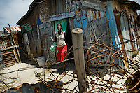 A Haitian woman leaves a shack in the slum of Cité Soleil, Port-au-Prince, Haiti, 16 July 2008. Cité Soleil is considered one of the worst slums in the Americas, most of its 300.000 residents live in extreme poverty. Children and single mothers predominate in the population. Social and living conditions in the slum are a human tragedy. There is no running water, no sewers and no electricity. Public services virtually do not exist - there are no stores, no hospitals or schools, no urban infrastructure. In spite of this fact, a rent must be payed even in all shacks made from rusty metal sheets. Infectious diseases are widely spread as garbage disposal does not exist in Cité Soleil. Violence is common, armed gangs operate throughout the slum.