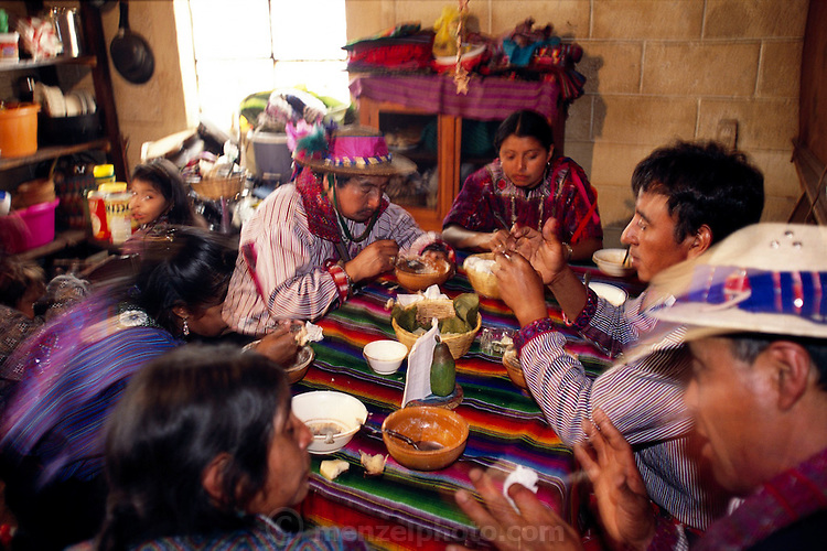 """The Mendoza kitchen in their home in  Todos Santos Cuchumatán, Guatemala, is the center of family life, and his wife's cooking unlocks the key to Fortunato's heart. """"I am happiest,"""" Fortunato (at right, center) says, """"when I'm eating Susana's rice and beans, her homemade tortillas, and her turkey soup."""" Hungry Planet: What the World Eats (p. 160)."""