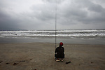 A fisherman waits for a bite on a stormy winter day in Da Nang, Vietnam. Dec. 23, 2012.