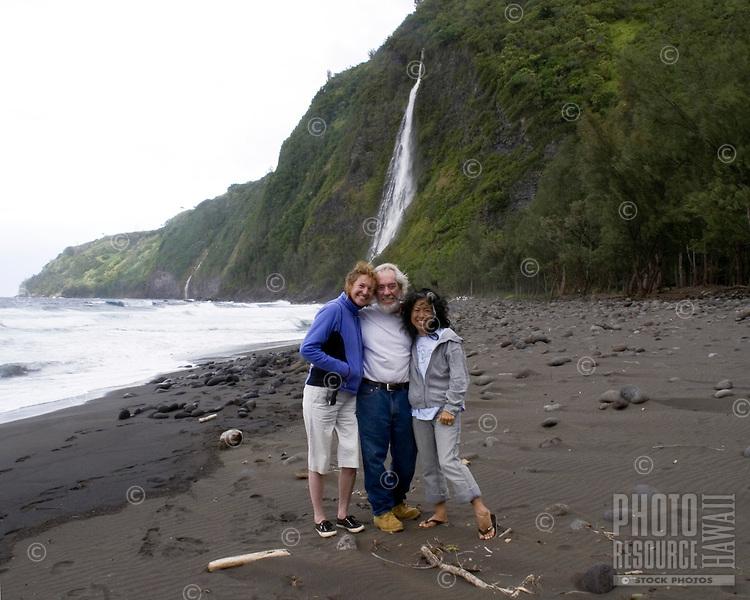 Three friends on a black sand beach with waterfall in Waipio