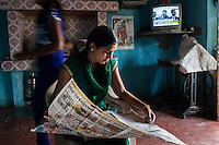 Video Volunteer videojournalist Niru J. Rathod, 24, reads the newspaper with the TV running news channels in the background as her sister Daksha (left), 15, walks past at home in Surendranagar, Gujarat, India on 14 December 2012. While Niru's sisters have become seamstresses or housewives, Niru, the 8th child in a family of 11 girls born to a Dalit construction worker, has been using videography for social change since 2006. She shoots and produces her own short documentaries and is a committed video activist, having conducted hundreds of village video screenings where she also speaks to thousands of men, shattering their ideas about what a woman and a Dalit can do while bringing massive changes to the communities she documents. Photo by Suzanne Lee / Marie Claire France