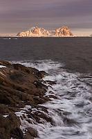 Mountains rise in distance above rocky coast outside Kabelvåg harbor, Austvågøy, Lofoten Islands, Norway