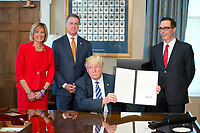United States President Donald J. Trump holds up the order after signing the first of three Executive Orders concerning financial services at the Department of the Treasury in Washington, DC on April 21, 2017.  From left to right: US Representative Claudia Tenney (Republican of New York) US Senator David Perdue (Republican of Georgia), the President, and US Secretary of the Treasury Steven Mnuchin.<br /> Credit: Ron Sachs / Pool via CNP /MediaPunch
