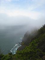 Ocean mist climbs the cliffs along the Pacific coastline.
