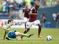 Colorado Rapids forward Sanna Nyassi tries to escape the tackle of Seattle Sounders FC midfielder Alvaro Fernandez during play CenturyLink Field in Seattle Saturday July 16, 2011. The Sounders won the game 4-3.