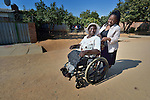 Edith Ncube had polio as a child and today uses a wheelchair in Bulawayo, Zimbabwe. Her wheelchair was provided by the Jairos Jiri Association with support from CBM-US. In this image she is pushed in the street by Deborah Sibanda, a community rehabilitation worker for Jairos Jiri.