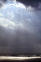 A dramatic sky full of clouds, rain and sun appears over the William Powell Bridge, part of the Rickenbacker Causeway that links Miami to the islands of Virginia Key and Key Biscayne, Florida.