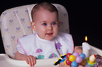 Girl,(12 months old) first birthday looking at cake and one lit candle, sitting in a highchair with surprised look on face, Lynnwood, Washington USA   MR