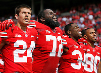 """Ohio State players, from left, kicker Drew Basil (24), defensive lineman Chris Carter (72), running back Carlos Hyde (34) and wide receiver Chris Fields (80), sing """"Carmen Ohio"""" following the Buckeyes' 76-0 win over Florida A&M in the NCAA football game at Ohio Stadium in Columbus on Sept. 21, 2013. (Adam Cairns / The Columbus Dispatch)"""