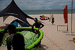 STORM Kiteboarding employees inflate surf kites while waiting for the wind to pick up in Mui Ne.