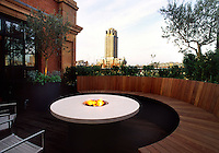 Wide angle view of decked roof terrace with a view across London