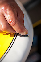 Sanding a repair to a small scratch on a stand up paddleboard.