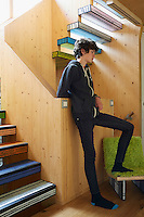 The artist Richard Woods has built a timber house where he can both create and showcase his bold, bright work.  Woods shares with his wife Jess Spanyol, a children's book author, and their three children. 14 year-old Milo stands in the hallway.