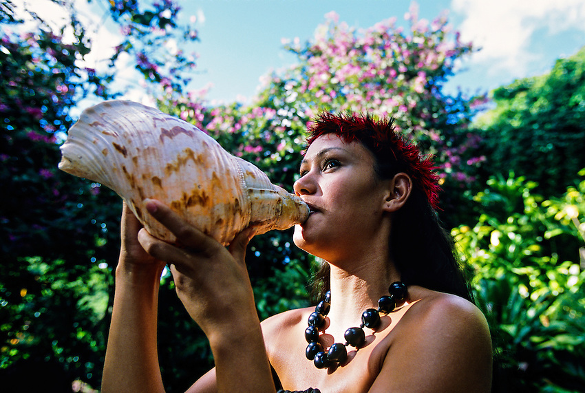 Hawaiian woman blowing conch shell, Waimea Falls Park, Waimea Bay, north shore of Oahu, Hawaii USA