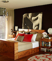 In the master bedroom the walnut-vener bed is piled with a collection of scatter cushions and a large contemporary photographic print is displayed on the black-painted wall behind