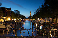 Typical Amsterdam canal scene - Westerkerk church, canal and bicycles along Prinsengracht in Amsterdam, Holland
