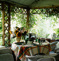 The delights of al fresco dining in this pergola in a London garden with a table set for an informal lunch