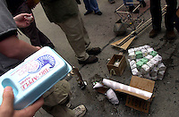 "Students from The Cooper Union Engineering School gather around the destroyed ""egg drop devices"" after the Annual Egg Drop Competition on April 29, 2003. The participants had to design and build a device to securely house a raw egg so that it could survive intact a three story drop from the portico of the school's Foundation building. (© Richard B. Levine)"