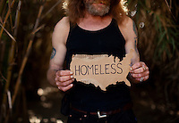 "Ventura, California, July 23, 2010 - A portrait of Tim 'Timbow' Bowman holding a cardboard map of the United States near his campsite along Ventura River bottom. Bowman has been homeless and living along the river since the early 1990's. In 1987 Bowman's 18-month-old daughter, Miranda Laurel, died from Lyme disease. His wife left him soon afterwards. A year later he fell through a plate glass window while working on a construction site, leaving him disabled and unable to work construction. He says the loss of his wife and daughter and his struggles with work sent him into a spiral. He eventually lost his home. He says he lives in the 300+ community along the river bottom because he ""feels at home."" Adding, ""I feel loved down here. Up there is nothing but trouble."" The two-mile stretch of river bottom from the Pacific to Stanley Road is home to about 300 homeless, who have carved tunnels and paths into the tall grass and bamboo. Bowman, who survives off of SSI, says, ""I lead an honest life. I don't steal, I don't rob and I share whatever I can."" .."