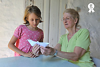 Grandmother teaching granddaughter origami (Licence this image exclusively with Getty: http://www.gettyimages.com/detail/91875439 )