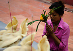 Woman prays at an offering table at a temple in rural Thaliand