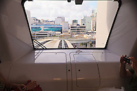 Tourists enjoy a ride in an automated Miami Metromover rail car as downtown Miami's shopping and commercial district looms in the car's front window.