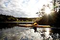 WA02473-00...WASHINGTON - Kayaker in a bydarka style boat exploring the waters of Garrison Bay San Juan Island.