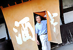 """Yasutaka Daimon, president and owner of Daimon Sake Brewery Co., walks through the """"noren"""" curtain at the entranceway to his Sakahan brewery in Mukune Village, Osaka, Japan on July 24 2008. Daimon is the 6th generation master brewer at Sakahan, which has been in existence for the best part of two centuries. Sakahan is a key exporter of sake, a wine-like alcoholic beverage fermented from rice, particularly to the U.S. where his popular Mukune brand is available in 44 states...Photographer: Robert Gilhooly"""