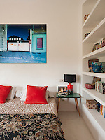 A large, brightly coloured, contemporary photograph is displayed on a wall above the bed